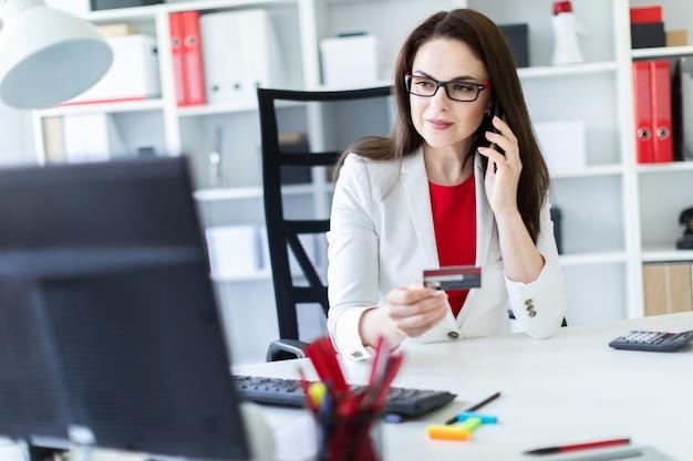Ein junges mädchen, das im büro am tisch sitzt und eine bankkarte und ein telefon hält.
