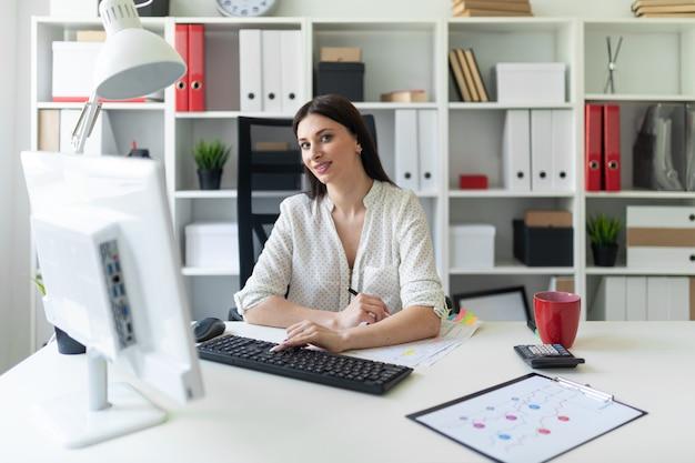 Ein junges mädchen, das im büro mit dokumenten und einem computer arbeitet.