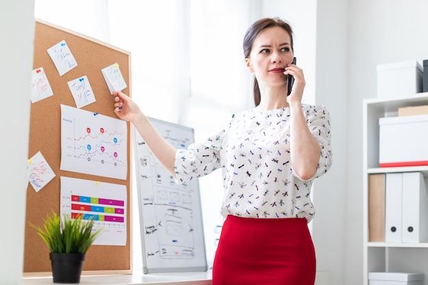 Ein junges mädchen, das im büro nahe dem brett mit aufklebern steht und am telefon spricht.