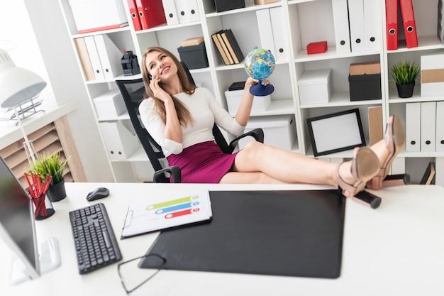 Ein junges mädchen, das im büro sitzt, die beine auf den tisch wirft und ein telefon und einen globus in der hand hält.