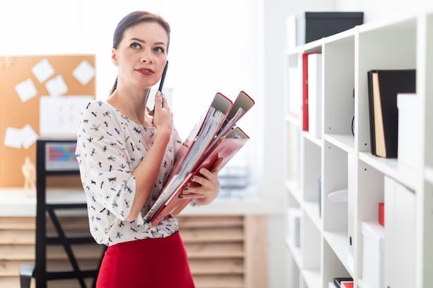 Ein junges mädchen, das im büro steht, am telefon spricht und einen ordner mit dokumenten hält.