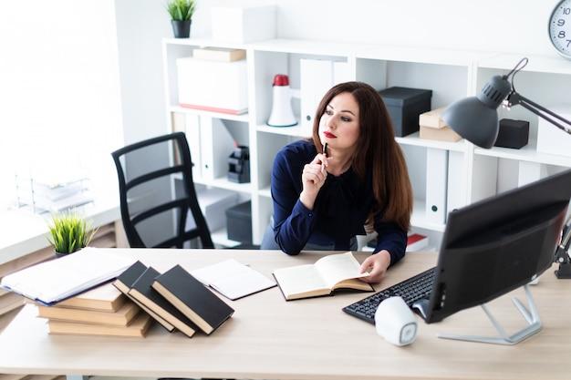 Ein junges mädchen, das nahe der tabelle steht und mit einem computer und einem tagebuch arbeitet.