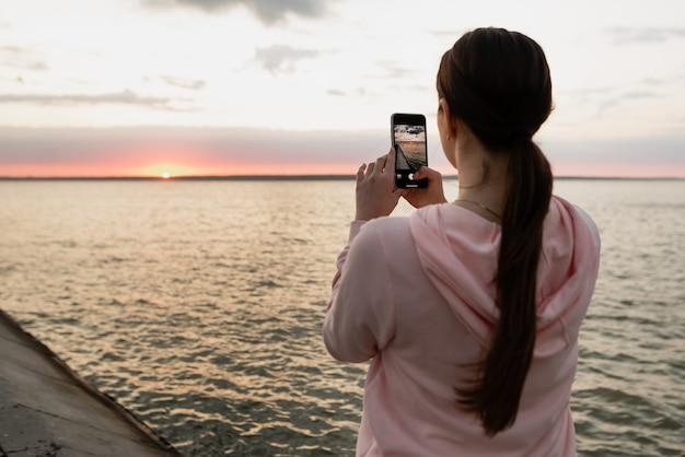 Ein junges mädchen, eine sportlerin, kam nach einer radtour ans meer, fotografierte die morgendämmerung, schaute auf das meer und ruhte sich vom sport aus.