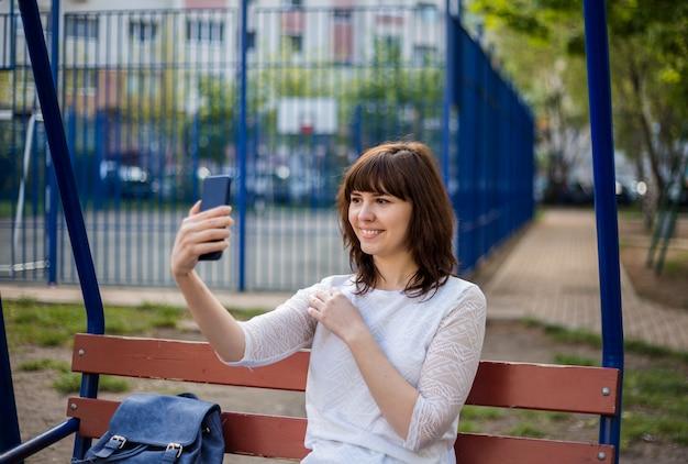 Ein junges mädchen fotografiert sich am telefon auf der straße. ein süßes mädchen sitzt auf einer bank und lächelt und hält ein telefon in ihren händen. ein mädchen in weißer jacke und jeans.