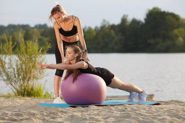 Ein junges mädchen führt mit hilfe eines lehrers übungen auf einem gymnastikball durch