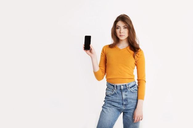 Ein junges mädchen hält ein smartphone. porträt eines mädchens mit einem telefon in ihren händen auf einem hellen hintergrund mit platz für text