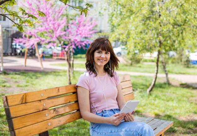 Ein junges mädchen hält ein tablet in den händen, kopfhörer in den ohren. nettes mädchen, das musik durch kopfhörer auf einem tablett hört. ein mädchen in einem rosa t-shirt und jeans sitzt auf einer bank auf der straße.