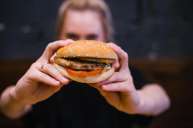 Ein junges mädchen hält einen burger mit einem fleischpastetchen in den händen. leckeres und herzhaftes mittagessen. fastfood und snacks.