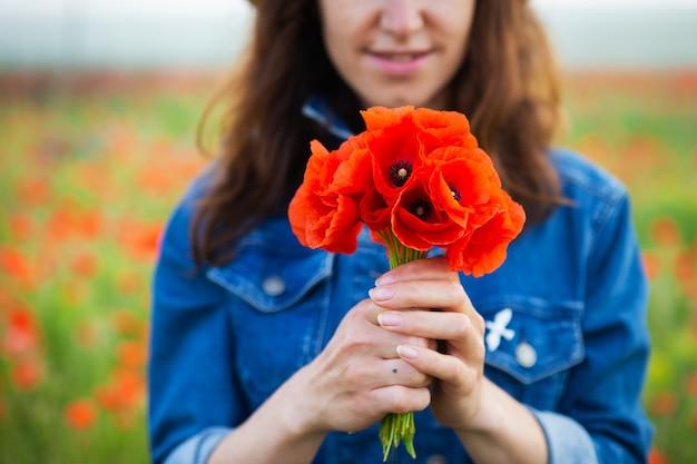 Ein junges mädchen hält einen strauß schöner roter mohnblumen in der hand vor sich. nahansicht.
