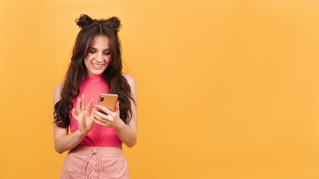 Ein junges mädchen hält ihr smartphone in den händen und schaut auf den bildschirm. das mädchen steht auf einem gelben hintergrund. eine kopie des raums. platz für ihren text.