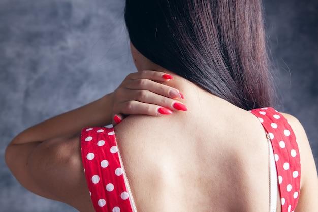 Ein junges mädchen hat nackenschmerzen