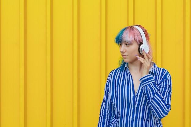 Ein junges mädchen hört ihre lieblingsmusik in großen weißen kopfhörern