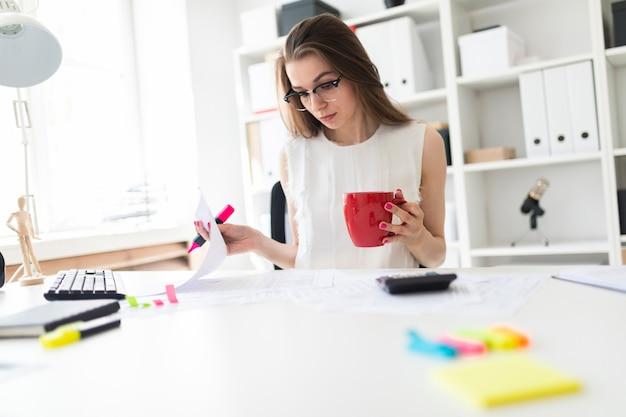 Ein junges mädchen im büro hält eine rosa markierung, eine rote tasse und arbeitet mit dokumenten.