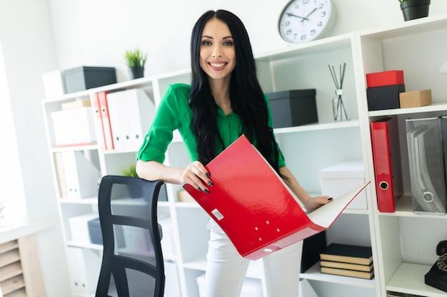 Ein junges mädchen im büro hält einen ordner mit dokumenten.