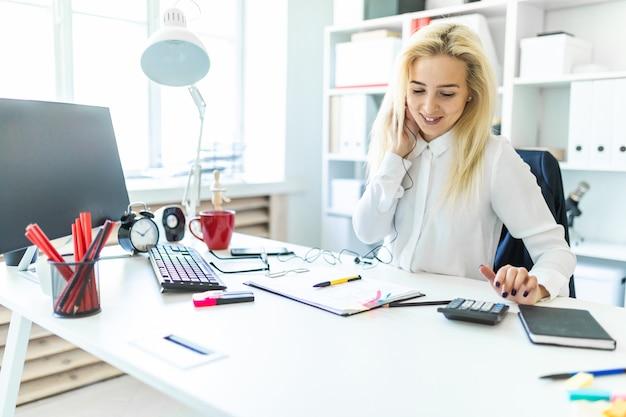 Ein junges mädchen im büro sitzt an einem tisch und telefoniert über ein headset und zählt auf einem taschenrechner.