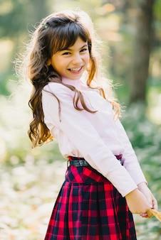 Ein junges mädchen im parkherbst lächelt