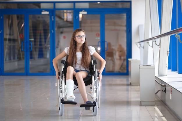 Ein junges mädchen im rollstuhl steht auf dem flur des krankenhauses.
