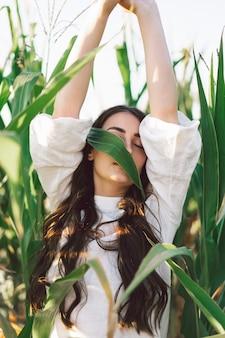Ein junges mädchen in einem getreidefeld. trend - mädchengesicht mit maisblättern. einheit mit der natur. umweltschutz