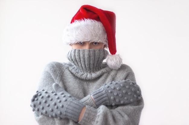 Ein junges mädchen in einem grauen strickpullover, handschuhen und einer roten weihnachtsmütze zog den kragen des pullovers über ihr gesicht und umarmte sich