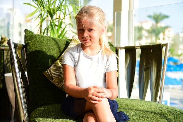 Ein junges mädchen in einem kleid sitzt auf einem sessel in einem sonnigen hotel.