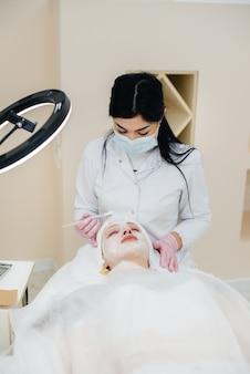 Ein junges mädchen in einem kosmetikbüro unterzieht sich einer gesichtsverjüngung. kosmetologie.