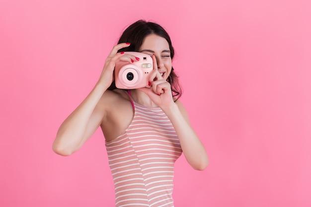 Ein junges mädchen in einem rosa gestreiften kleid hält eine kamera in ihren händen