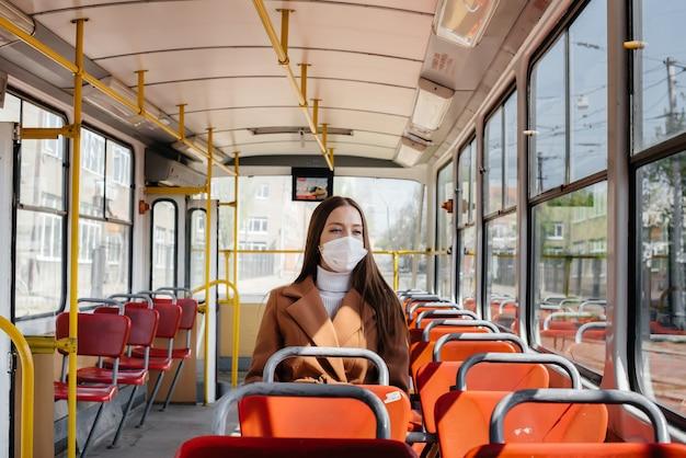 Ein junges mädchen in einer maske benutzt während einer pandemie allein die öffentlichen verkehrsmittel. schutz und prävention 19.