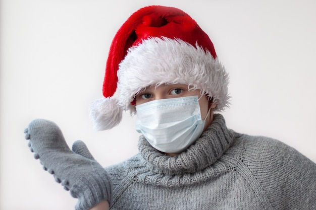 Ein junges mädchen in einer weihnachtsmütze und einem grauen pullover mit einer medizinischen maske hob die hand