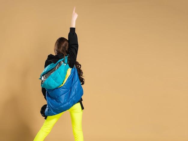 Ein junges mädchen in gelben leggings und einer warmen weste hebt die hand mit dem zeigefinger und dreht den rücken gegen eine pastellorange.