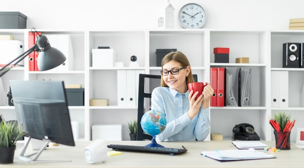 Ein junges mädchen in gläsern sitzt an einem tisch, hält eine rote tasse in den händen und betrachtet den globus.