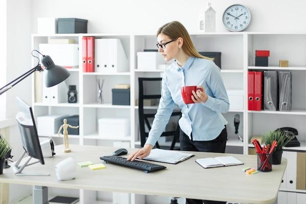 Ein junges mädchen in gläsern steht in der nähe des tisches, hält eine rote tasse in der hand und tippt auf der tastatur.