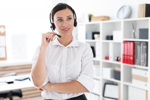 Ein junges mädchen in kopfhörer mit mikrofon ist in einem hellen büro.