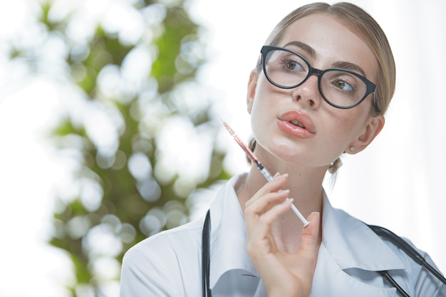 Ein junges mädchen ist eine kosmetikerin mit brille und einem weißen kittel mit einer spritze in der hand