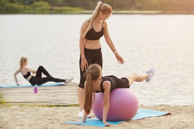 Ein junges mädchen macht eine übung mit einem gymnastikball mit einem trainer