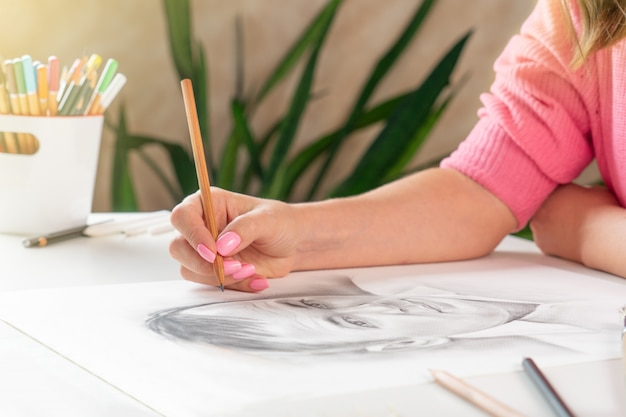 Ein junges mädchen malt ein porträt eines mannes mit einem bleistift in einem hellen heimstudio.