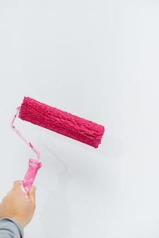 Ein junges mädchen malt eine weiße wand in rosa mit einer rollennahaufnahme. reparatur des innenraums.