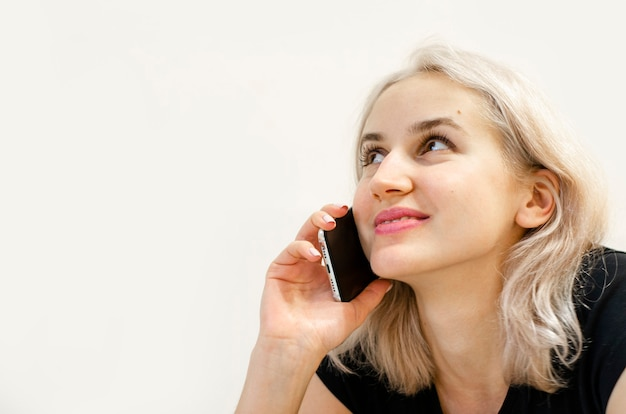 Ein junges mädchen mit blonden haaren kommuniziert am telefon. fröhliches gespräch. virtuelle kommunikation. ohne das haus zu verlassen. weißer hintergrund.