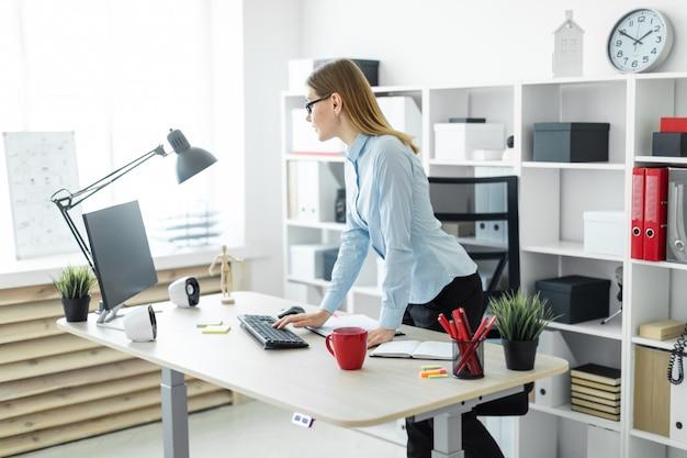 Ein junges mädchen mit brille steht neben dem tisch und druckt auf der tastatur.