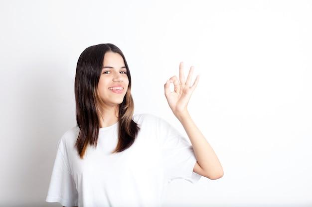 Ein junges mädchen mit dunklen haaren in einem weißen t-shirt zeigt ok und lächelt weißer hintergrund