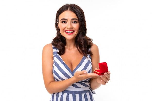 Ein junges mädchen mit einem entzückenden lächeln, flachen zähnen, rotem lippenstift, langen gewellten kastanienbraunen haaren, wunderschönem make-up in einem weiß-blauen kleid in einem streifen mit einer dekolleté hält eine rote ringschachtel in den händen