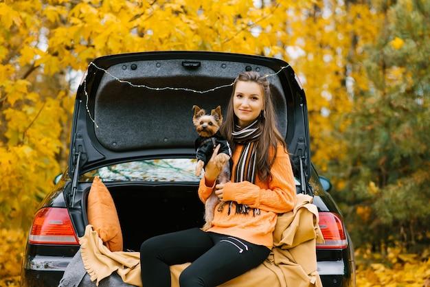 Ein junges mädchen mit einem hund sitzt im kofferraum eines autos vor dem hintergrund eines herbstwaldes. haustier und menschliche freundschaft