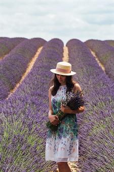 Ein junges mädchen mit einem lavendelstrauß steht mitten auf einem lavendelfeld
