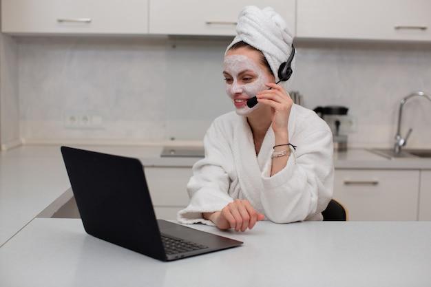 Ein junges mädchen mit einer feuchtigkeitsspendenden maske im gesicht in einem weißen gewand, das über das headset spricht, das hinter einem laptop arbeitet, der in der küche sitzt, hochwertiges foto
