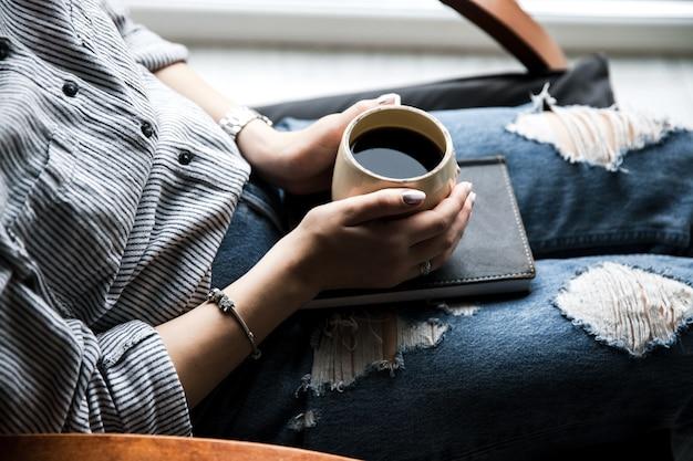 Ein junges mädchen mit einer schönen maniküre hält ein buch mit einer tasse kaffee. modestil