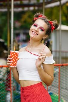 Ein junges mädchen mit hellen make-up und eine fröhliche frisur zwei gulki hält einen hellen pappbecher in den händen, und in der anderen hand hält rote brille und.