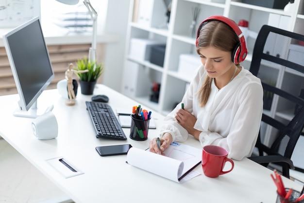Ein junges mädchen mit kopfhörern sitzt an einem tisch im büro und zeichnet eine markierung auf ein blatt.