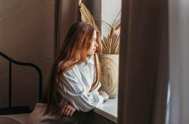 Ein junges mädchen mit langen haaren, das nach dem aufwachen im bett sitzt und im fenster auf die stadt schaut, zuhause am frühen morgen, lebensstil
