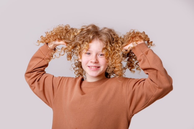 Ein junges mädchen mit lockigem haar lächelt und versucht es auf einem weißen hintergrund