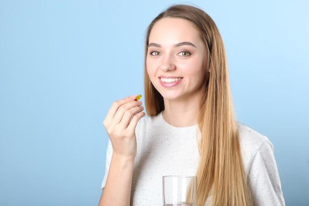 Ein junges mädchen nimmt nahrungsergänzungsmittel mit omega-kapseln ein