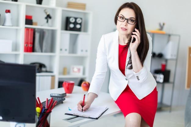 Ein junges mädchen setzte sich auf einen schreibtisch im büro und hielt ein telefon in der hand.
